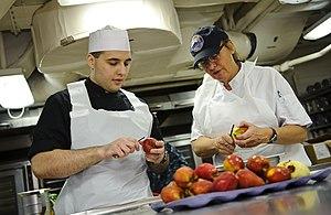 US Navy 111211-N-GC412-118 Culinary Specialist Seaman Matthew Ryback trains alongside Master Baker Chef Leslie Bilderback in the bakeshop aboard th.jpg