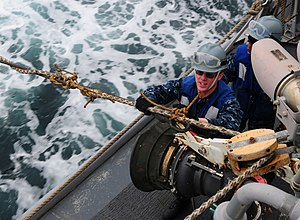 US Navy 120213-N-SK590-094 Boatswain's Mate 2nd Class Cory Johnson ties a messenger line to a fuel receiver during a replenishment at sea.jpg