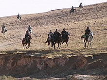Ten horses with riders on the side of a hill