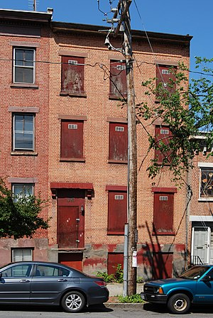 Urban blight (rowhouse with boarded windows an...
