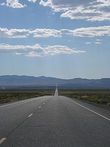 View across a desert valley with a highway proceeding straight for many miles towards the horizon and a distant mountain range