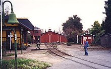 An elderly man standing next to railroad track in the foreground with an old-fashioned railroad depot building on the opposite side. A roundhouse and water tower are located where the railroad track ends in the background.