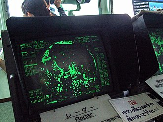 Radar display - This image shows a modern PPI display in use, with the islands and ground surrounding the ship in green. The current direction of the radar can be seen as the dotted line pointing northwest.