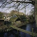 Zicht op de achterzijde van de schuur met diverse bijgebouwtjes en op de omgrachting met houten loopbrug - Nuis - 20401872 - RCE.jpg