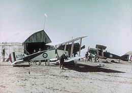 Two military biplanes parked by a tent