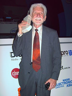Advanced Mobile Phone System -  Dr. Martin Cooper of Motorola made the first private handheld mobile-phone call on a larger prototype model in 1973. (The image shows a reenactment.)