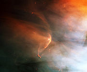 Patchy orange and blue nebulosity against a black background, with a curved orange arc wrapping around a star at the center.