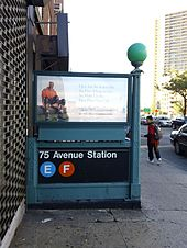 Staircase entrance to the 75th Avenue station, descending below street level. This entrance is located on the north side of Queens Boulevard.