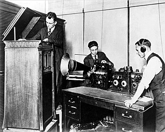 WWJ (AM) - August 1920 publicity photograph. L-R: Howard J. Trumbo, manager of the local Thomas A. Edison Record Shop, operating a phonograph player; Elton M. Plant, Detroit News employee and announcer, behind 8MK's DeForest OT-10 radio transmitter; and engineer Frank Edwards.