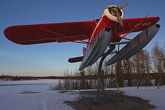 A Noorduyn Norseman attached to a display stand. Bush planes provide short-haul transport to the many lakes in the region. A308, Floatplane on display stand at sunset, Thompson, Manitoba, Canada, 2013.JPG