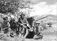 Four soldiers, dressed warmly with three of them wearing steel helmets, in front of a 2 pounder anti tank gun