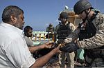 A U.S. Sailor, right, with the visit, board, search and seizure team assigned to the guided missile destroyer USS Mason (DDG 87) inspects a broken water pump assembly aboard a civilian dhow Nov. 23, 2013, in 131123-N-PW661-019.jpg