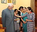 A delegation of visually impaired children of the National Association for the Blind, pinning a flag on the Vice President, Shri Mohd. Hamid Ansari, in New Delhi on September 22, 2015.jpg