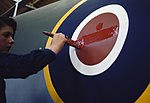A young woman worker painting the fuselage roundel on a Mosquito aircraft at de Havilland's factory at Hatfield in Hertfordshire, 1943. TR918.jpg
