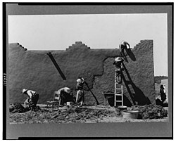Remudding an adobe wall in Chamisal, circa 1940. Photo: Russell Lee
