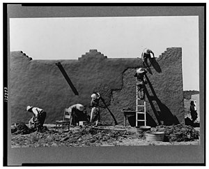Chamisal, New Mexico - Remudding an adobe wall in Chamisal, circa 1940. Photo: Russell Lee