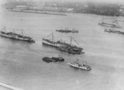 An overhead photograph of eight ships. At the bottom of the photograph is one side of a harbor with the ships in the water. Five ships are displaying decorative bunting. At the top of the photograph is the opposite side of the harbor.