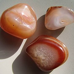 A group of tumble polished agates showing banding in red, orange and white with crystal interiors.