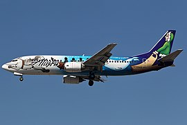Right side view of a Boeing 737 with a livery of sled dogs pulling a canoe and beluga whale, against a blue sky