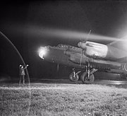 An Avro Lancaster Mk III of No. 49 Squadron RAF is guided to its dispersal point at Fiskerton, Lincolnshire, after returning from a raid on Berlin, 22 November 1943. CH11642