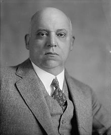 A black and white image of a bald man in his fifties wearing a suit