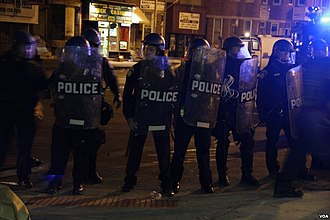 2015 Baltimore protests - Baltimore riot policemen form a line to push back protesters and media members on April 28