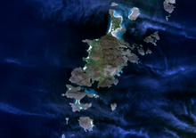 A large, dark green island seen from above is surrounded by smaller islands in a dark blue body of water. Wispy clouds partially obscure the view.