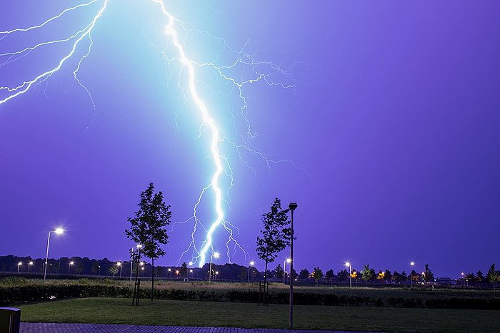 Lightning as an example of plasma present at Earth's surface: Typically, lightning discharges 30 kiloamperes at up to 100 megavolts, and emits radio waves, light, X- and even gamma rays. Plasma temperatures can approach 30000 K and electron densities may exceed 10 m . Bliksem in Assen.jpg