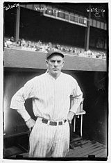 A man in a white baseball uniform stands in front of a dugout with his hands on his hips.