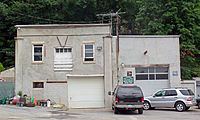 A gray building with two sections, both with large garage doors. A small green sign on the front of the smaller section, to the right, indicates that it is a registered New York State motor vehicle repair shop. Two cars are parked in front of that section, and behind the building is woods