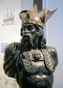Buste en bronze d'un chef gaulois torse nu, avec une longue moustache et des cheveux longs ainsi qu'un casque celtique de couleur plus claire avec deux ailes latérales.