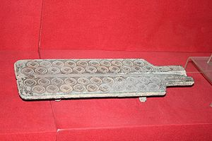 Economy of the Han dynasty - A Han dynasty bronze mold for making wuzhu (五銖) coins; the latter featured a square hole in the center so that strings could pass through and thus allow one to carry many coins at once.