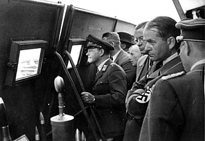 Speer (right, with arms folded and swastika armband) looks on with Field Marshal Erhard Milch (left) during weapons testing. - Albert Speer