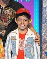A smiling, young Indian boy wearing a red t-shirt, blue and white jacket, and red hat.