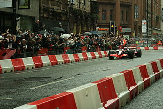 Deansgate - Jenson Button drives a McLaren F1 car down Deansgate