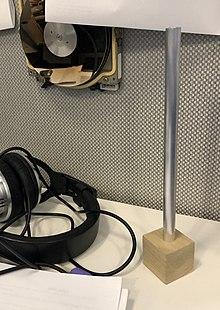 An aluminum (silver) desktop Festivus pole with a square natural walnut base on a desktop in an office cubilcle.