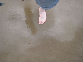 English: Foot stepping on wet sand causing san...