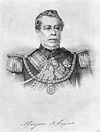 Lithograph depicting head and shoulders of a man with gray moustache wearing a military tunic with epaulettes and elaborate lanyards, several medals at his neck and breast, sash of office, and a prominent star on a heavy gold chain suspended from his shoulders