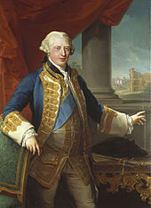 A three-quarter portrait of a young man. His hair is light grey/blonde. He wears pale leggings, a pale waistcoat decorated with gold lace, a large blue sash, and a blue and gold lace blazer. His right arm rests on a chair, his left hand points to a painting behind him.
