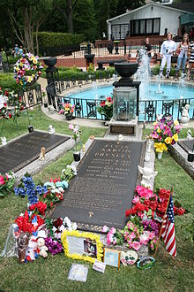 "A long, ground-level gravestone reads ""Elvis Aaron Presley"", followed by the singer's dates, the names of his parents and daughter, and several paragraphs of smaller text. It is surrounded by flowers, a small American flag, and other offerings. Similar grave markers are visible on either side; in the background is a small round pool, with a low decorative metal fence and several fountains."