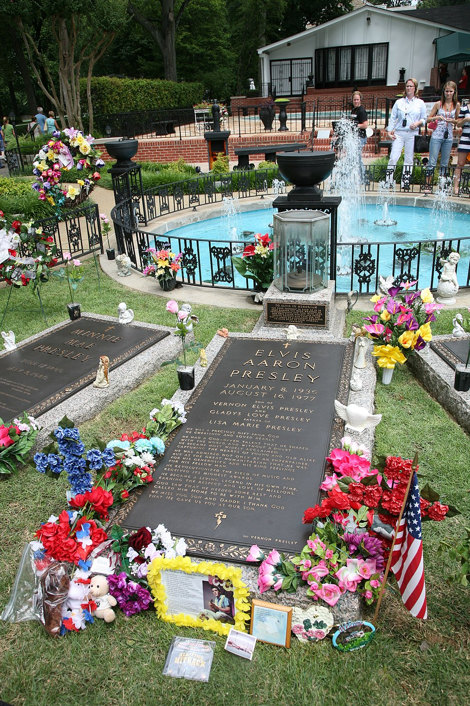 """A long, ground-level gravestone reads """"Elvis Aaron Presley"""", followed by the singer's dates, the names of his parents and daughter, and several paragraphs of smaller text. It is surrounded by flowers, a small American flag, and other offerings. Similar grave markers are visible on either side. In the background is a small round pool, with a low decorative metal fence and several fountains."""