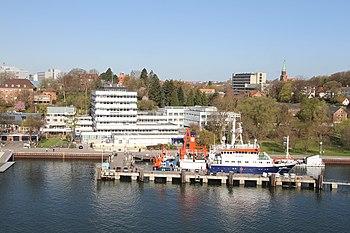 """Das Geomar mit Aquarium an der Kiellinie, davor das Forschungsschiff """"Alkor"""""""