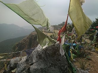 George Everest - Park House as seen through  weathered Tibetan Buddhist prayer flags, placed by Mussoorie's longtime Tibetan community, from a vantage point at an angle above.