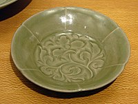 A green-grey plate with a leafy vine pattern painted into the center. The edge is divided into six sections, each arched slightly outward, to create the illusion that they were flower petals.