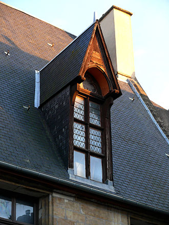 Flashing (weatherproofing) - The flashing visible here is the apron below the dormer and the valley flashing in the open valley. The step flashing (soakers) are properly installed underneath the roof and wall shingles and thus is not visible. Hôtel Demoret Moulins, France