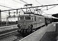HUA-167993-Afbeelding van de electrische locomotief nr. 1129 (serie 1100) van de N.S. met een trein langs het perron van het N.S.-station Roosendaal te Roosendaal.jpg