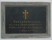 A dark granite tombstone with Chinese writing
