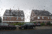 Houses and cars seen through a rain-streaked car window.jpg