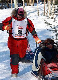 Iditarod musher David Sawatzky running up the hill near the Northern Lights overpass (3419755733).jpg
