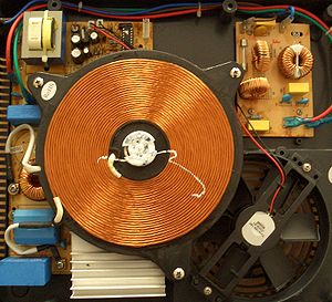 Induction cooking - Inside view of an induction cooker: the large copper coil forms the magnetic field, a cooling fan is visible below it, and power supply and line filter surround the coil. In the centre of the coil is a temperature sensor, covered in white thermal grease